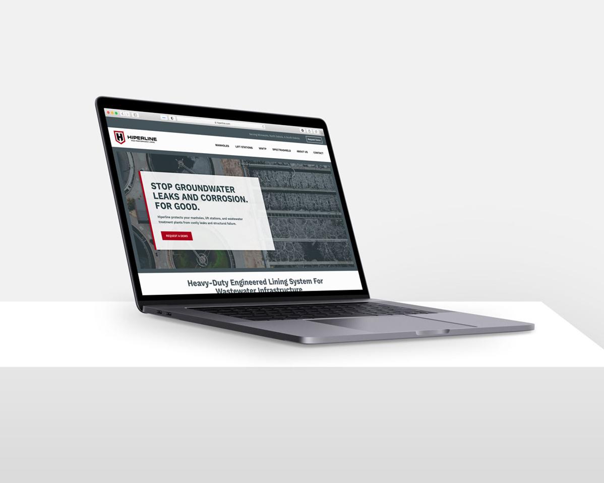 Laptop with Hiperline website mockup on screen